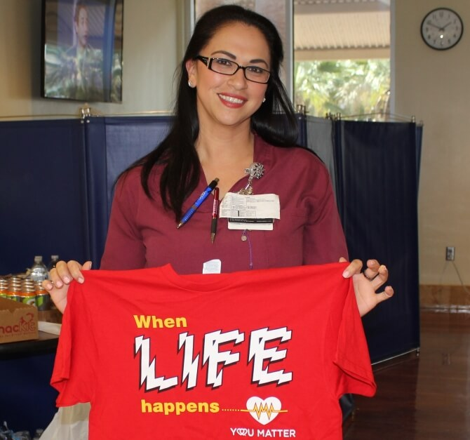 Woman holding blood drive charity t-shirt